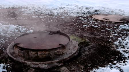 придорожный : Close-up steam is from sanitary sewer cover in snow. Melted snow around. Стоковые видеозаписи