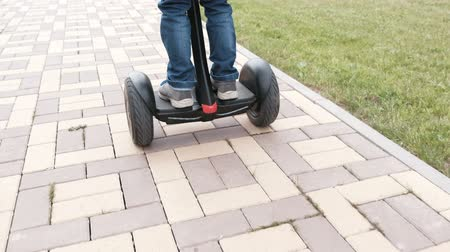 self balancing : Unrecognizable boy is rolling on gyro scooter near the home. Back view. Legs close-up. Stock Footage