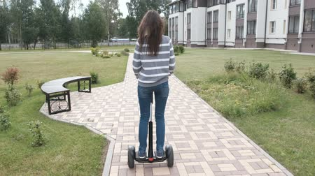 self balancing : Brunette woman is rolling on gyro scooter near the home, back view.