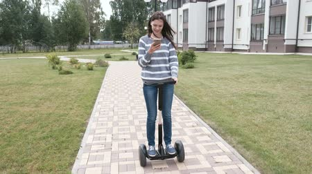 gyroscope : Beautiful brunette woman is rolling on gyro scooter near the home and looking at mobile phone.