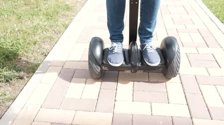 gyroscope : Persons legs in sneakers rolling on gyro scooter on paving road. Stock Footage