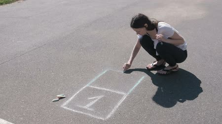 sandalet : Woman draws a hopscotch on the asphalt with colorful chalks.