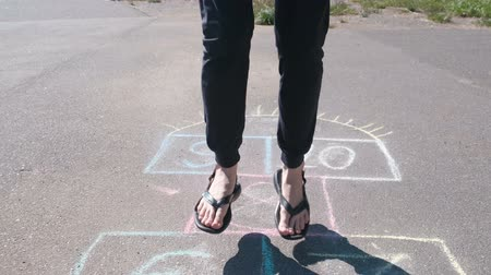 sandalet : Girl teenager jumps playing hopscotch in the street. Close-up legs. Front view.