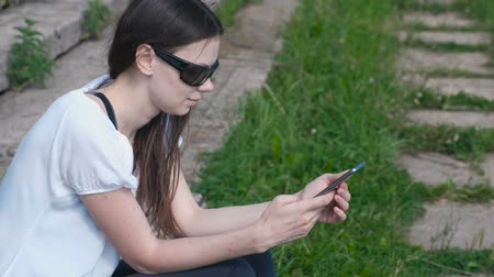 schoolyard : Woman types a message on phone sitting in park. Stock Footage