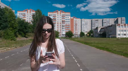 go to school : Young brunette girl walking in the stadium in a residential area and talking on a mobile phone.