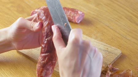 harmful : Womans hands are peeling the smoked sausage from peel.
