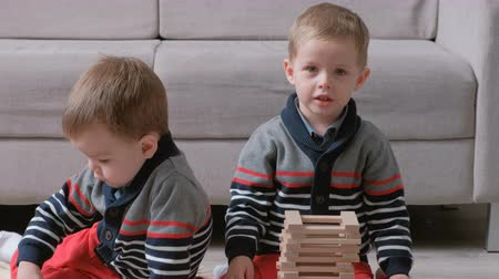 sitting floor : Twins boys brothers are building from wooden blocks sitting on the floor by the sofa in their room.