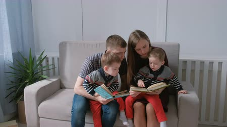 biblia : Family mom, dad and two twin brothers read books sitting on the sofa. Family reading time.