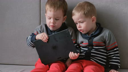 kavga : Two twin brothers toddlers playing together games on tablet sitting on the sofa.