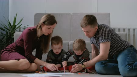 dvojčata : Family mom, dad and two twin brothers draw together markers and felt pens sitting on the floor. Dostupné videozáznamy