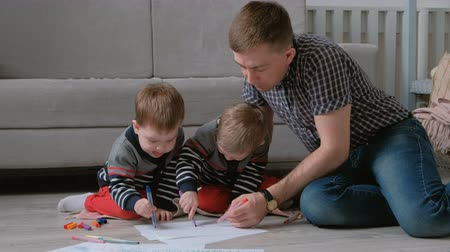 dvojčata : Family dad and two twin brothers draw together markers and felt pens sitting on the floor. Dostupné videozáznamy