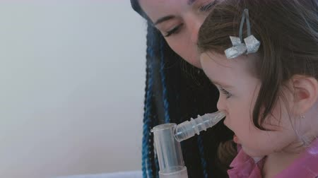 dýchání : Little cute girl inhaling through inhaler mask with her mom. Use nebulizer and inhaler for the treatment.