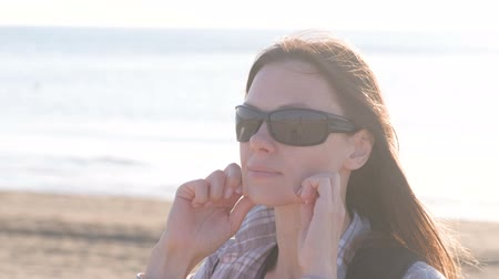 łokieć : Woman doing a facial massage herself on the beach. Close-up view face.