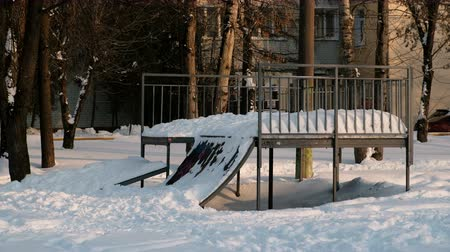 gravado : Skate boarding park in snowy sunny winter city Park. Snow drifts on the hill to skateboard.