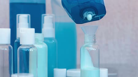 kompakt : Womans hands pour blue shampoo in a small bottle of big through a funnel. Travel set of jars. Bottle close-up.