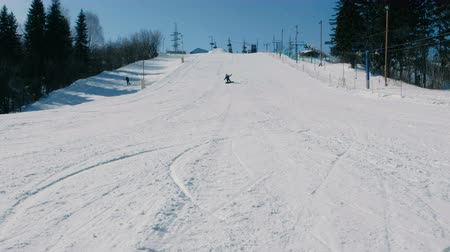 склон : Teenage boy of 12 years in blue suit sliding on a snowboard from snow descent next sky lift. View from afar. Стоковые видеозаписи