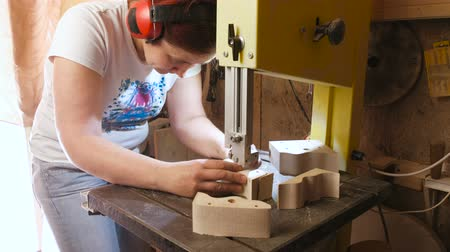 craftswoman : Craftswoman is cutting a wood toy cars workpiece from wood with bandsaw.