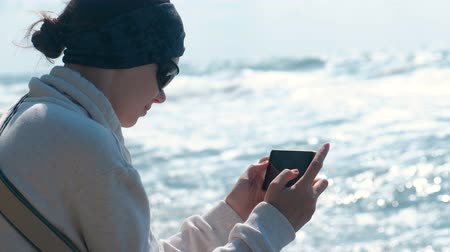 wizerunek : Woman photographs the sea and the waves sitting on the shore.