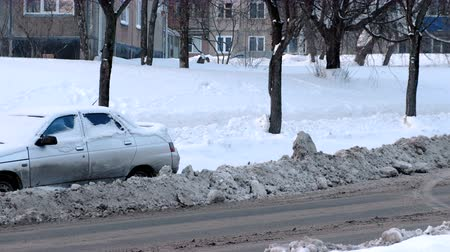 bairro : Snow-covered car on the side of a snowy road.