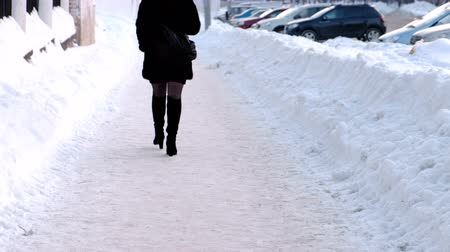 fur boots : Unrecognizable woman walking down the street in boots and nylon tights in winter on snowy street.