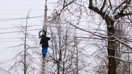 утилита : Man repair of power lines in the city in winter. Stands on a ladder with a wire in his hands, back view.