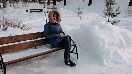 covering : Woman is sitting on bench in winter city park during the day in snowy weather with falling snow.