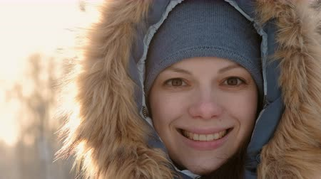 иней : Close-up woman face in fur hood looking in camera and smiling in winter park. Right on video.