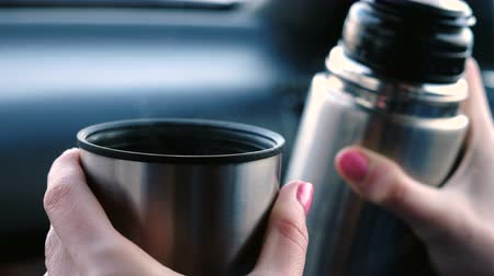хорошее настроение : Closeup view of womans hands keeping a cup of hot tea and thermos sitting in the car in winter.