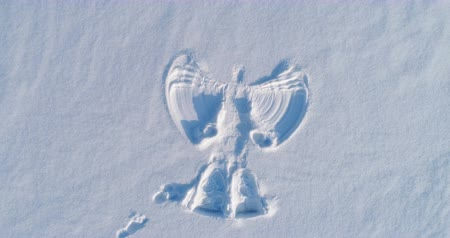 ślady stóp : Snow angels print on a snowcovered area. Aerial footage. Camera gradually moves away.