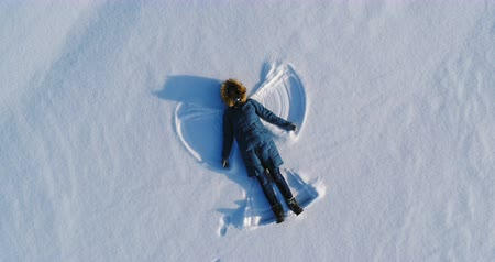 ślady stóp : Woman makes snow angel laying in the snow. Aerial video. Camera moves away slowly.