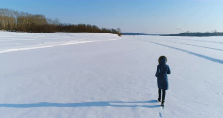 flee : Aerial footage of running woman in winter landscape of a frozen river with a forest and a view of the city with factories. Back view.