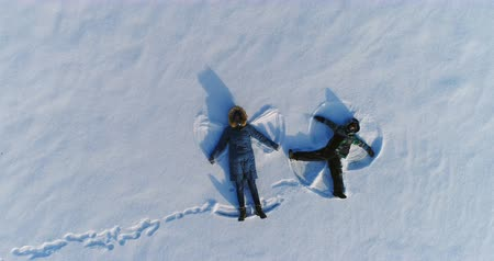 flee : Mom and son make snow angels together. Camera slowly rising. Aerial footage.