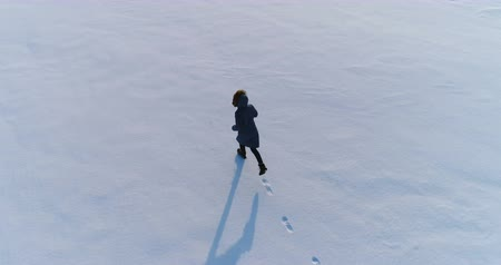 flee : Woman running on a snow covered area. Aerial video. Back view.