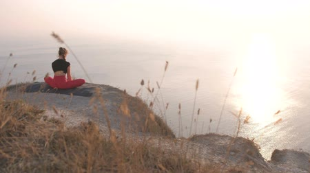 kötött : Beautiful view of woman doing yoga Baddha Konasana Bound Angle Pose on the mountain with sea view at sunset. Back view.