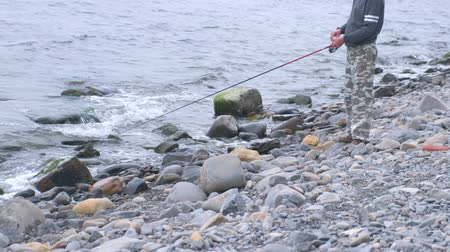 dull : Unrecognizable Man is fishing rod on the sea beach. Stock Footage