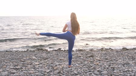 小石 : Girl is doing exercise lunge, leg lift the bodyflex during breathing exercises on the sea background.