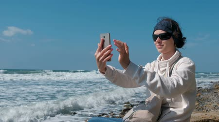 photograph : Woman makes selfie sitting by the sea on stone beach in autumn.