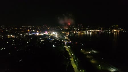 ünnepélyes : Festive fireworks in a small town on the coast at night. Aerial view of the city, sea and fireworks.