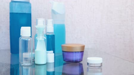 reutilizável : Pour blue shampoo in a small bottle of big through a funnel. Travel set of jars. Bottles of cosmetics close-up.