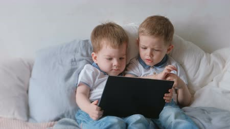 dvojčata : Kids with tablet. Two boys twins toddlers looking cartoon at tablet lying on the bed. Dostupné videozáznamy