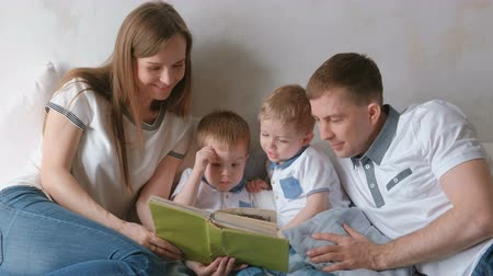 stories : Family mom, dad and two twin brothers read books laying on the bed. Family reading time.