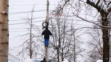 lineman : Man repair of power lines in the city in winter. Stands on a ladder with a wire in his hands, back view.