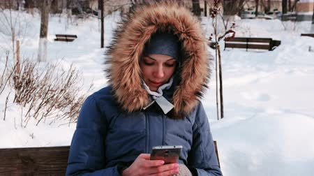 congelado : Closeup woman is sitting on bench and browsing mobile phone in winter park in the city during the day in snowy weather with falling snow.