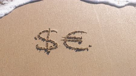 gazdasági pangás : Euro and Dollar signs written in the sea sand. Waves washed away the inscription. Stock mozgókép