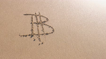 gazdasági pangás : Bitcoin sign written in the sea sand. Waves washed away the inscription.