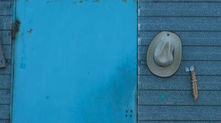 vstoupit : Concept of the cowboy lifestyle. Old blue wood door. Cowboy hat and knife near the door.