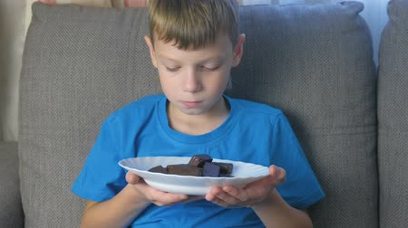 słodycze : Boy with character. Teen looks at candy and smell them. Concept of unhealthy eating.