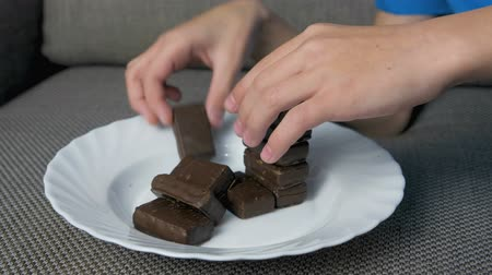 açucarado : Boys hand building a tower of chocolate candies on a white plate on the sofa.