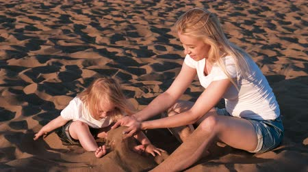 коршун : Beautiful blonde mom and daughter play with sand sitting together on the beach. Стоковые видеозаписи