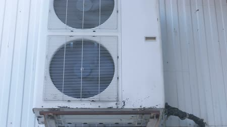 фэн : Old air conditioning on the street side. Fans are behind bars. Close-up view.
